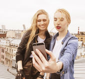 Dos amigos de muchachas reales rubios frescos que hacen el selfie en el top del tejado, concepto de la gente de la forma de vida Foto de archivo