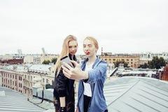 Dos amigos de muchachas reales rubios frescos que hacen el selfie en el top del tejado, concepto de la gente de la forma de vida Fotos de archivo
