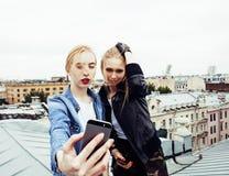 Dos amigos de muchachas reales rubios frescos que hacen el selfie en el top del tejado, lif Foto de archivo