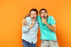 Dos amigos del asombro que abrazan, sosteniéndose la barbilla y mirando c imagen de archivo libre de regalías