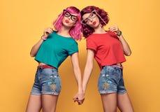 Dos amigos del inconformista de las muchachas que se divierten con los apoyos fotografía de archivo
