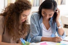 Dos amigos diversos felices de la universidad de las muchachas que estudian junto en campus imágenes de archivo libres de regalías