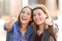 Dos amigos divertidos con los pulgares para arriba imagen de archivo libre de regalías