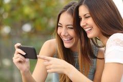 Dos amigos divertidos de las mujeres que ríen y que comparten medios en un teléfono elegante Foto de archivo