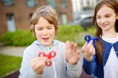 Dos amigos divertidos que juegan con los hilanderos de la persona agitada en el patio Juguete de tensión-alivio popular para los  Fotografía de archivo