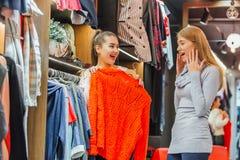 Dos amigos eligen los suéteres durante compras Encontrando un suéter anaranjado de la muchacha feliz Siéntase bien, sonrisa y ris imagen de archivo