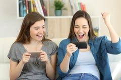 Dos amigos emocionados que juegan juegos y ganar Fotografía de archivo libre de regalías