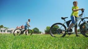 Dos amigos en ciclo montan en campo de hierba verde juntos metrajes