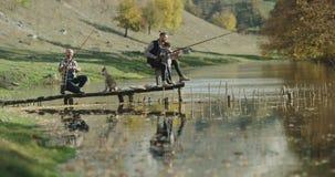 Dos amigos, en el medio de la montaña que pesca en un pequeño lago, un niño pequeño lindo que se coloca por otra parte de su papá metrajes