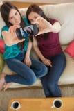 Dos amigos en el sofá que toma un selfie con smartphone Imagenes de archivo