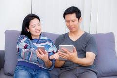Dos amigos en línea con los dispositivos múltiples y sentarse que habla en un sofá Imagen de archivo libre de regalías