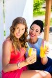 Dos amigos en la playa del lago que se relaja con las bebidas Imagenes de archivo