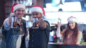 Dos amigos en los sombreros de Papá Noel y la muchacha detrás del metrajes