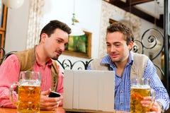Dos amigos en pub bávaro con la computadora portátil imagenes de archivo