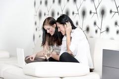 Dos amigos en un ordenador portátil en casa Fotos de archivo