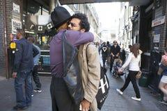 Dos amigos encontrados en el carril del ladrillo Un hombre en un sombrero alto y un hombre en vidrios se abrazan como saludo Fotografía de archivo libre de regalías