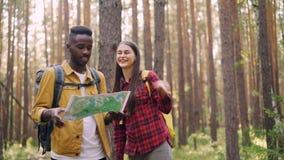 Dos amigos están mirando el mapa en bosque, están señalando en la misma dirección, están riendo y están caminando juntos activo almacen de video