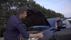 Dos amigos están reparando una situación quebrada del coche en el encintado que el individuo muestra que un finger hasta su hombr metrajes