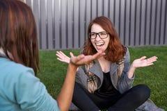 Dos amigos felices de la mujer que ríen junto en un parque con un fondo verde Foto de archivo