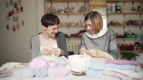 Dos amigos felices de la mujer tienen ropa de las lanas de la diversión que hace punto en el estudio casero almacen de metraje de vídeo