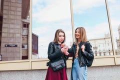 Dos amigos felices de las mujeres que comparten medios sociales en un teléfono elegante al aire libre en ciudad Dos mujeres joven Fotografía de archivo