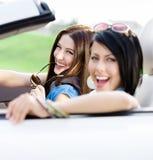 Dos amigos felices montan el coche Imagenes de archivo