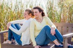 Dos amigos felices que se sientan en el banco de parque que habla y que obra recíprocamente Fotografía de archivo
