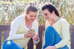 Dos amigos felices que se sientan en el banco de parque que habla y que obra recíprocamente Imagen de archivo
