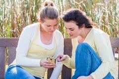 Dos amigos felices que se sientan en el banco de parque que habla y que obra recíprocamente Imagenes de archivo