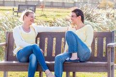 Dos amigos felices que se sientan en el banco de parque que habla y que obra recíprocamente Fotos de archivo