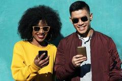 Dos amigos felices que usan el móvil en la calle Concepto de la amistad fotografía de archivo libre de regalías