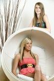 Dos amigos femeninos alrededor de la silla del estilo del huevo Foto de archivo