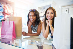 Dos amigos femeninos atractivos que hacen compras junto Foto de archivo