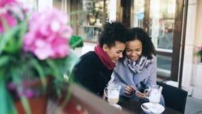 Dos amigos femeninos de la raza mixta atractiva que comparten junto usando smartphone en café de la calle al aire libre Imagen de archivo