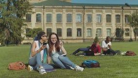 Dos amigos femeninos de la universidad que cotillean en c?sped del campus metrajes