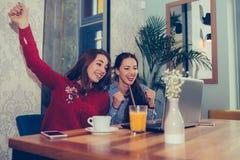 Dos amigos femeninos elebrating noticias de la lectura del éxito buenas en un ordenador portátil fotografía de archivo libre de regalías