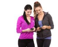 Dos amigos femeninos en el fondo blanco Foto de archivo libre de regalías