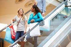Dos amigos femeninos en la escalera móvil en alameda de compras Imagen de archivo