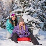 Dos amigos femeninos en nieve del invierno del trineo Fotos de archivo libres de regalías