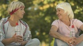 Dos amigos femeninos en ropa de deportes que hablan después de entrenamiento afuera, sentándose en parque metrajes