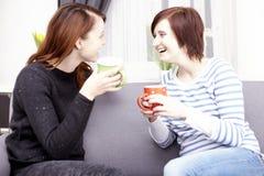 Dos amigos femeninos felices con las tazas de café Foto de archivo libre de regalías