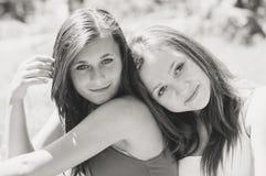 Dos amigos femeninos felices que abrazan en verano verde parquean Imágenes de archivo libres de regalías