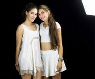 Dos amigos femeninos felices que presentan en estudio en el vestido blanco Fotos de archivo