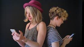 Dos amigos femeninos hermosos jovenes que se colocan de nuevo a trasero y que mecanografían en el teléfono, aislado en fondo almacen de metraje de vídeo