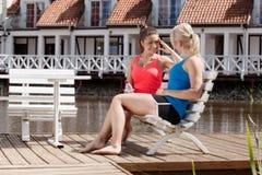 Dos amigos femeninos hermosos que descansan sobre banco y hablar Imagenes de archivo