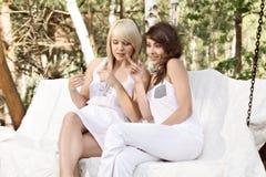 Dos amigos femeninos hermosos que descansan sobre el oscilación y hablar Imagen de archivo libre de regalías