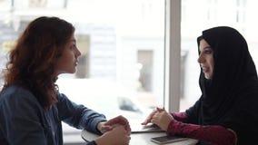 Dos amigos femeninos internacionales que hablan en café: la mujer musulmán joven en hijab negro está hablando con su caucásico fe metrajes