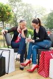 Dos amigos femeninos jovenes atractivos que disfrutan de un día hacia fuera después de compras acertadas Imagen de archivo libre de regalías