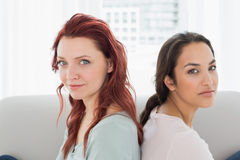 Dos amigos femeninos jovenes hermosos que se sientan de nuevo a la parte posterior Foto de archivo libre de regalías