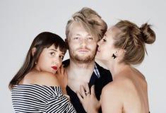 Dos amigos femeninos jovenes que abrazan a un hombre - Imagen de archivo libre de regalías